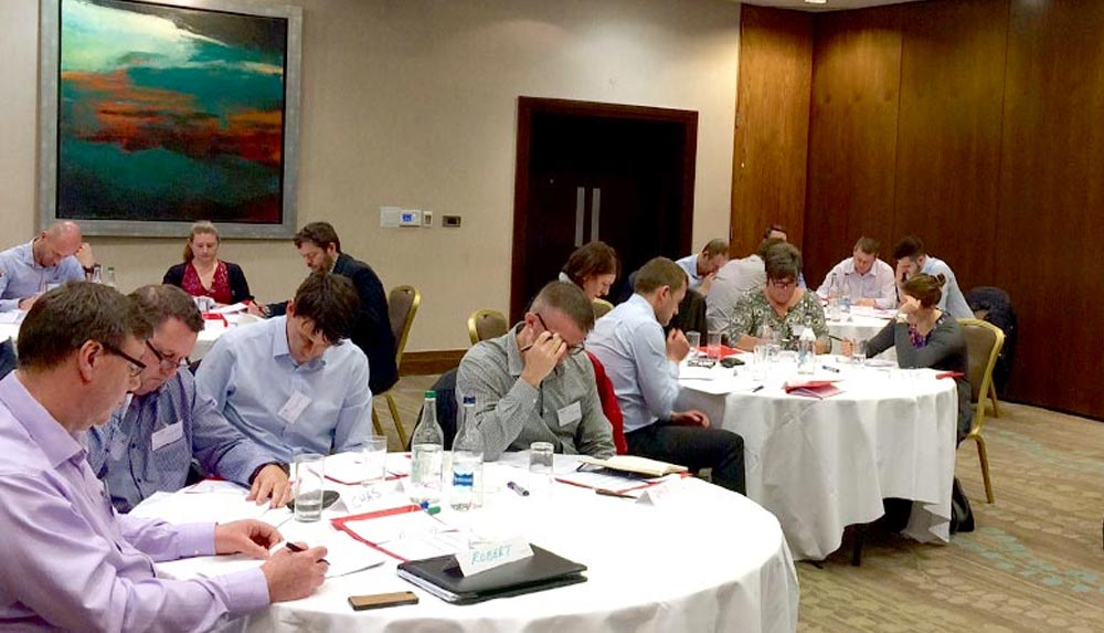 Delegates are seated at small round tables on the strategic management training course